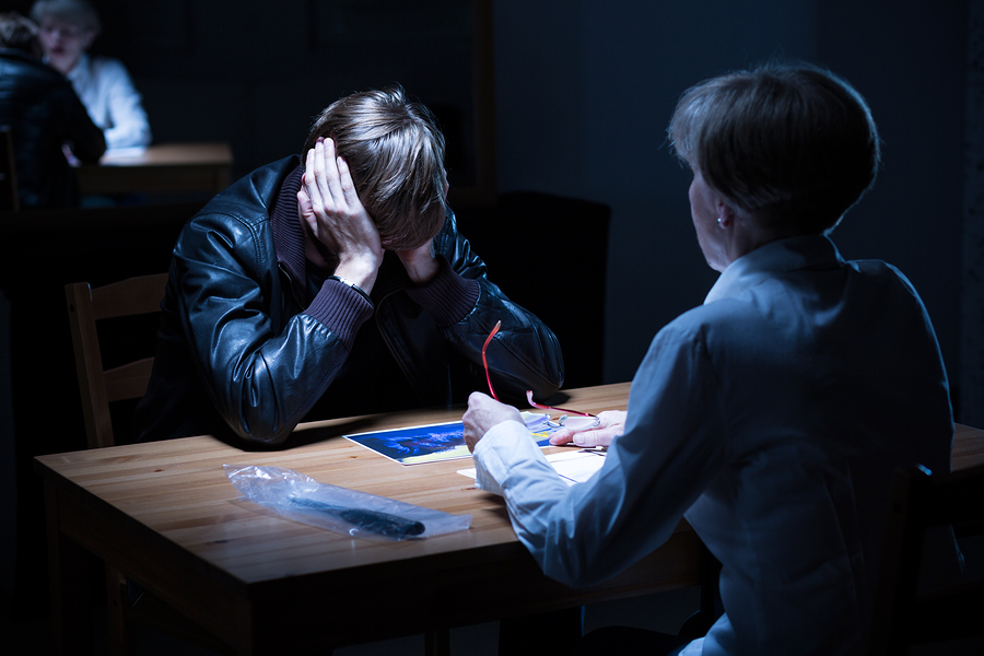 Woman discussing juvenile crimes with a young man in a black leather jacket in a dark police interrogation room.